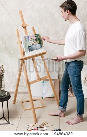 Artist draws a beautiful painting on easel. Young man stands by easel and drawing still-life picture in art studio. Painter's workshop, new masterpiece, creativity and leisure concept