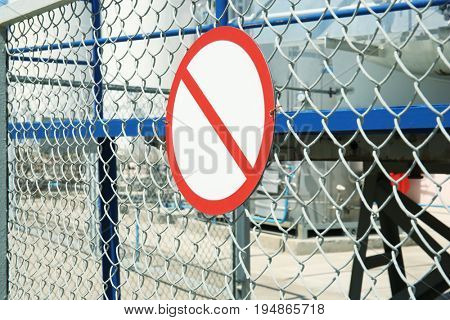 Warning sign on fence of production facility