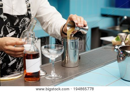 Bartender is pouring infusion into a mixing glass