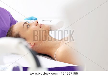Cosmetic clinic, woman during laser facial surgery.