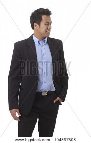 Asian businessman with hand in pocket looking left, smiling.