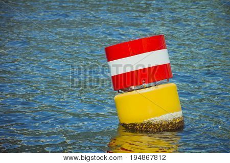Yellow Red And White Steel Navigational Floating Buoy In The Blue Sea Water