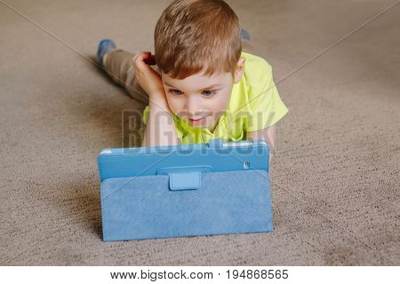 Portrait of cute adorable white Caucasian toddler boy lying on floor playing with digital tablet with funny face expression. Candid lifestyle early development. New technology generation.