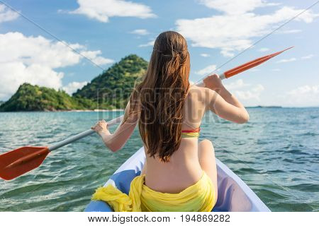 Rear view of a young woman paddling with a double-bladed paddle a canoe on the sea during summer vacation in Flores Island, Indonesia