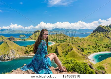 Rear view of a young woman enjoying the awesome view of Padar Island while sitting on the top of a volcanic mountain during summer vacation in Indonesia