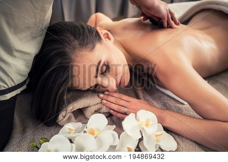 Young woman lying down while receiving hot stone massage at Asian spa and wellness center