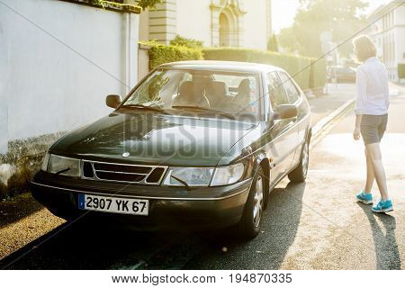 STRASBOURG FRANCE - MAY 2017: Female wearing casual clothes approaching Saab 900 a compact luxury automobile which was produced by Saab from 1978 until 1998 in two generations beautiful sun flare light behind