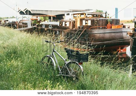 Vintage bike parked near liveaboard boat on a river - summer travel discovery of unusual places