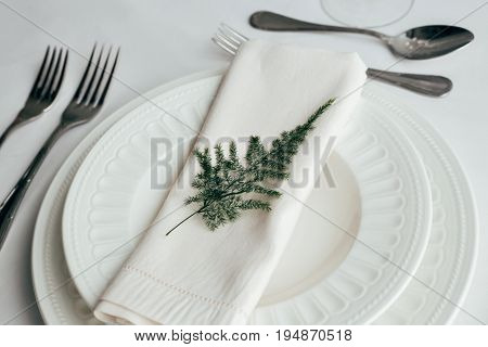 Neatly assembled white porcelain china plates with cutlery and silk napkin decorated and served for dinner or fancy lunch in expensive gourmet restaurant