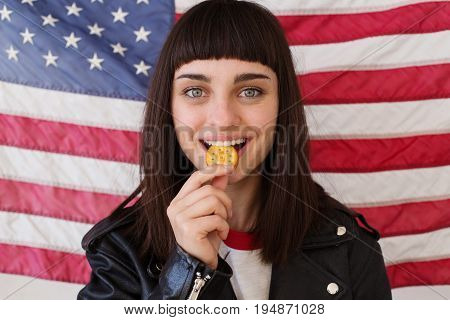 Petite female woman or teenager in trendy hipster outfit eats poses with crunchy peanut butter cookie cracker typical traditional american snack with usa flag