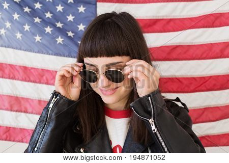 Feminine beautiful woman or teenage girl wears new sunglasses eyewear on background of american flag trendy and fashionable hipster patriot of usa