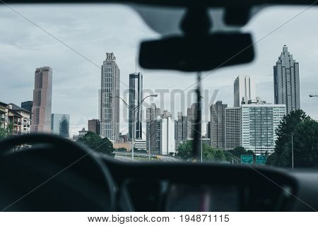 POV shot from inside car on driver going in traffic towards downtown of american city atlanta with glass office and finance buildings and skyscrapers concept business and success