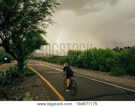 Strong female cyclist athlete rides her carbon aero bike on empty road into distance just after rain heavy monsoon clouds during hard training