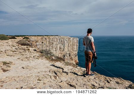 Adventure inspired photographer man with professional gear camera stands on edge of cliff ready to make photos of seaside beautiful views