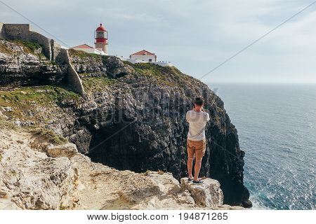 Professional handsome man photographer stands on rocks and cliffs overlooking red lighthouse on edge of mountain in sea inspiration and adventure lifestyle