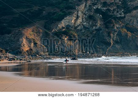 Very wide and open beach with tide line and mountain rock surfer walks towards waves with his surfing board ready to take on adventures