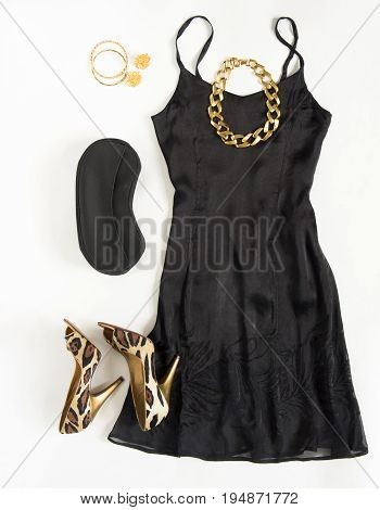 Christmas party outfit. Cocktail dress outfit night out look on white background. Little black dress black clutch leopard shoes gold necklace bracelets and earrings. Flat lay top view