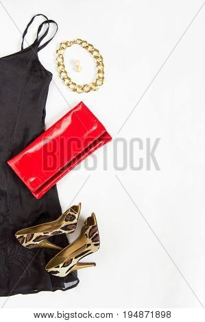 Cocktail dress outfit night out look on white background. Little black dress red clutch leopard shoes gold necklace and earrings. Flat lay top view