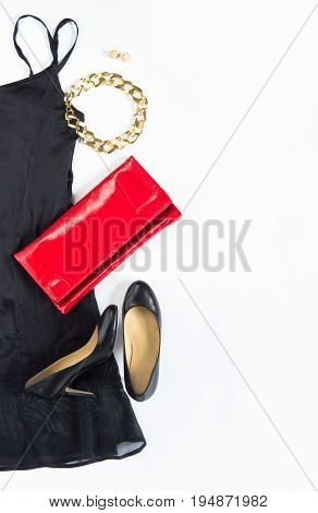 Cocktail dress outfit night out look on white background. Little black dress red clutch black shoes gold necklace and earrings. Flat lay top view