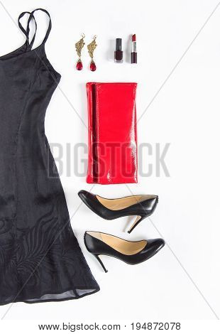 Evening dress outfit night out look on white background. Little black dress red clutch black shoes earrings lipstick and nail polish. Flat lay top view