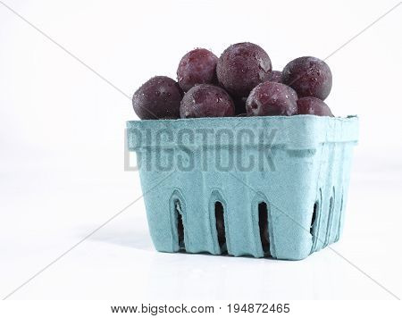 A Green Container with Multiplie Fresh Plums