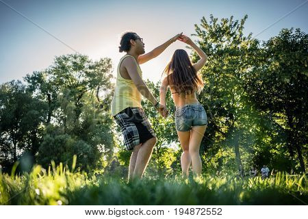 Mann turning woman dancing in the grass in summer park