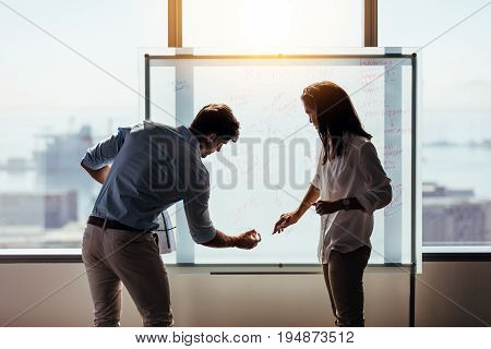 Man and woman entrepreneurs writing business ideas on whiteboard. Business investors discussing business ideas in office.