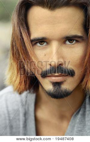 attraktiver Mann mit langem Haar und Schnurrbart
