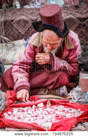 Leh, Ladakh, India, July 12, 2016: local man is selling crystals on a sidewalk market in Leh, Ladakh district of Kashmir, India