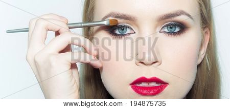 Girl With Red Lips Applying Eyeshadows With Makeup Brush