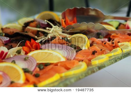 Table set for brunch with smoked salmon lox, capers, lemons, dill (shallow depth of field)
