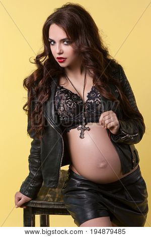 Provocative look of pregnant woman. Portrait of rock style girl in black leather jacket