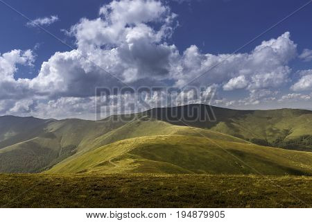 Summer view of Carpathian Mountains and Valleys, under blue sky with clouds. Mountain road goes on top of the hills on sunset landscape