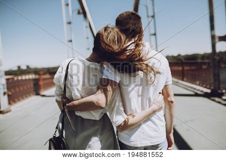 Stylish Couple In Love Hugging, Back View With Windy Hair, On Bridge In The Summer City. Modern Woma