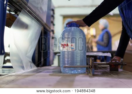 ST. PETERSBURG, RUSSIA - JUNE 29, 2017: Worker prepares can for packaging in the drinking water factory of Lider-Aqua  LTD. The factory is certified by regional quality certification program