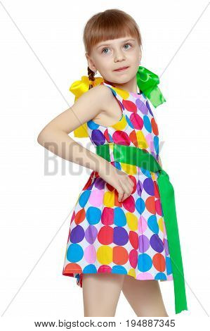 A happy little blonde girl with long pigtails, in which large colorful bows are braided, and a short bangs on her head. In a short summer dress, a pattern of multi-colored circles.