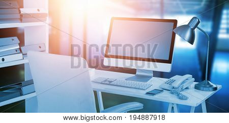 Computer with telephone and mobile phone at desk against a large room where is the meeting point
