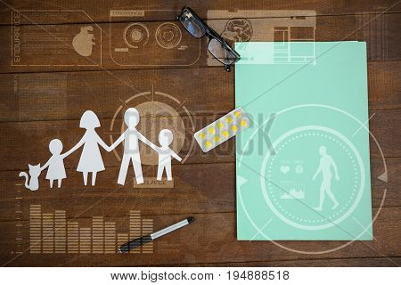 Human body organ development illustration against black background against paper cut out family chain with medicine and file on table