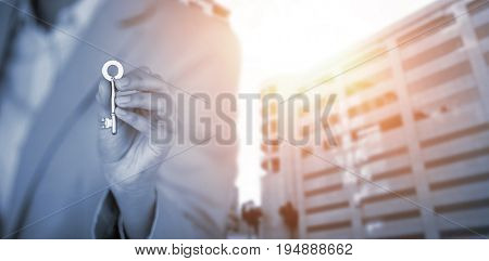 Mid section of business executive showing house key against glass modern building against cloudy sky
