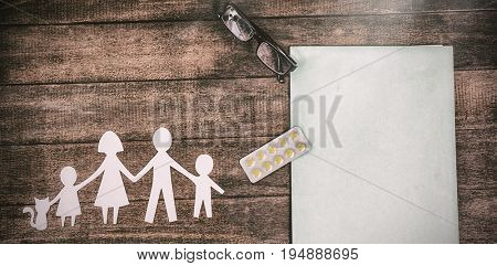 Overhead view of paper cut out family chain with medicine and file on table