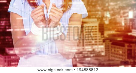 Mid section of businesswoman with tied hands against illuminated building in city at night