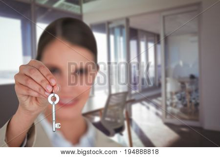 Close up of businesswoman showing new house key against interior of modern office