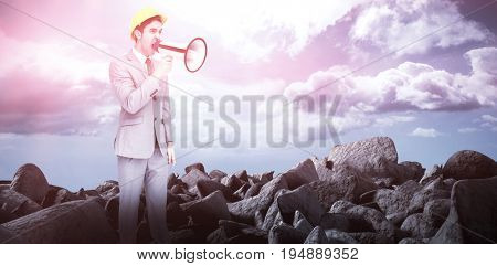 Young architect yelling with a megaphone against blue sky