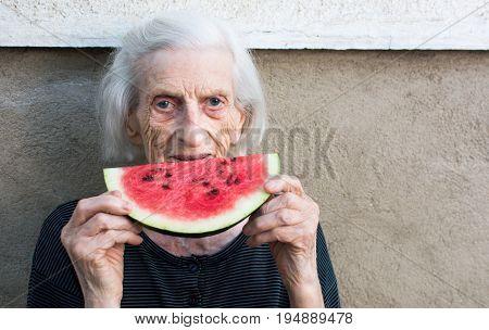 Cheerful Grandma Eating Watermelon In The Backyard