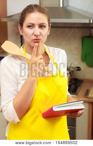 Housewife woman with cookbook and wooden spoon thinking in kitchen. Pensive mature female in apron at home.