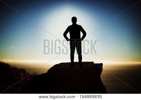 Silhouette businessman with hand on hip  against scenic view of mountain by sea against sky
