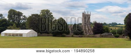 Newton St. Philip church and village green. Idyllic English village with ancient church of St. Philip and St. James and cricket pitch Somerset UK