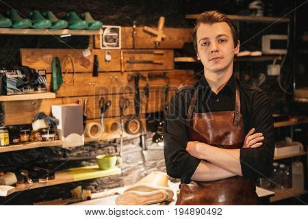Photo of young handsome man shoemaker at footwear workshop. Looking at camera.