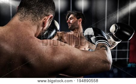 Strong boxer punches his opponent during boxing competition
