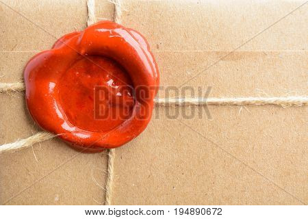 Close Up View Of Parcel Wrapped In Craft Paper With Rope And Red Sealing Wax
